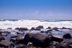 Wellen, die über Felsen an einem sonnigen Tag brechen lizenzfreies stockbild
