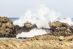 Wellen, die über Felsen an einem warmen sonnigen Tag brechen Lizenzfreie Stockbilder