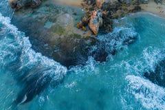 Wellen, die über Felsen zerquetschen stockfotos