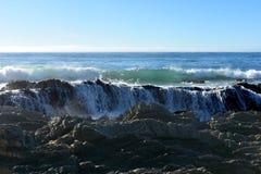 Wellen, die über felsiger Küstenlinie brechen Lizenzfreie Stockfotografie