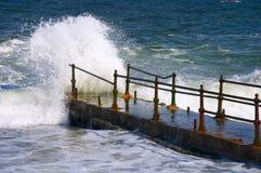 Wellen, die über Kai schlagen Stockfotografie