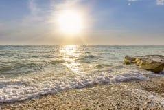 Wellen, die auf dem Pebble Beach einhüllen Stockfotos