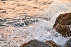 Wellen, die auf den Felsen bei Sonnenuntergang zusammenstoßen lizenzfreies stockfoto