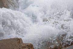 Wellen, die auf den Felsen brechen stockbild