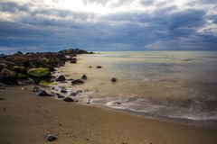 Wellen, die auf den Felsen und dem Strand zusammenstoßen stockfotos