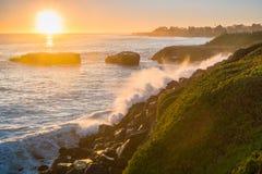 Wellen, die auf der felsigen Küstenlinie bei Sonnenuntergang, Santa Cruz, Kalifornien zerquetschen stockbild