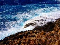 Wellen, die auf der Küstenlinie zusammenstoßen Stockbilder