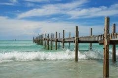 Wellen, die auf die Ufer- und Holzbrücke auf Meer zusammenstoßen Lizenzfreie Stockfotografie