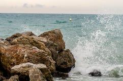 Wellen, die auf einem Felsen brechen Stockbild