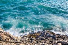 Wellen, die auf einem felsigen Strand zerquetschen stockbild