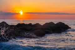 Wellen, die auf einem Riff bei Sonnenaufgang spritzen Stockfotos