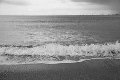Wellen, die auf einem sandigen Strand an einem bewölkten Tag zusammenstoßen Lizenzfreies Stockfoto