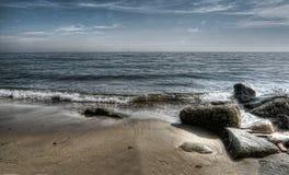 Wellen, die auf einem sandigen Strand einhüllen lizenzfreie stockfotos