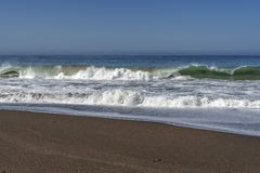 Wellen, die auf einem sandigen Strand macht Gischt zusammenstoßen lizenzfreie stockfotos