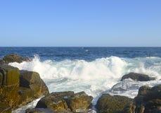 Wellen, die auf einem steinigen Strand brechen Lizenzfreie Stockfotografie