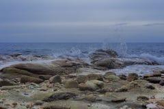 Wellen, die auf einem steinigen Strand brechen Stockfotos