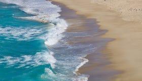 Wellen, die auf einen sandigen Strand - Bild einh?llen lizenzfreies stockbild