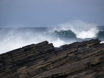 Wellen, die auf Felsen abbrechen Stockbilder