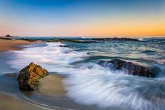Wellen, die auf Felsen bei Sonnenuntergang, bei Victoria Beach zusammenstoßen Stockfotos