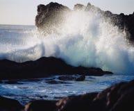 Wellen, die auf Felsen an der Küste zusammenstoßen lizenzfreies stockbild