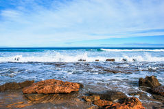 Wellen, die auf Felsen, perfekter blauer Ozean, Felsen am Ufer zusammenstoßen, Altostratuswolken im Himmel, Stockfotos