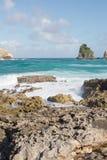 Wellen, die auf Felsen am tropischen Strand brechen Stockfotos
