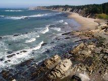 Wellen, die auf felsigem Strand brechen Stockfoto