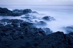 Wellen, die auf felsiger Küste an der Dämmerung abbrechen Lizenzfreie Stockbilder