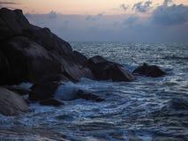 Wellen, die auf Küstensteinen bei Sonnenaufgang zusammenstoßen lizenzfreie stockbilder