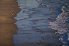 Wellen, die auf sandigem Strand brechen stockfoto