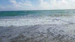 Wellen, die auf sandigem Strand landen stock footage