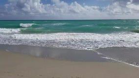 Wellen, die auf sandigem Strand landen stock video