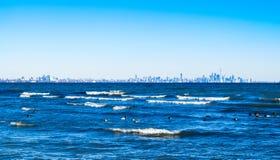 Wellen, die auf See mit Toronto-Skylinen auf fernem Horizont brechen Stockfotos