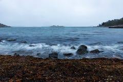 Wellen, die auf Steinen brechen Stockfotografie
