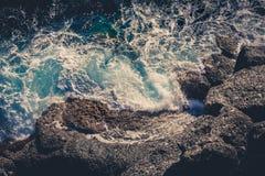 Wellen, die das Brechen auf den Felsen zerschmettern Brummenluftoberflächenansicht Lizenzfreies Stockbild