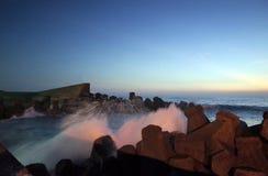 Wellen, die das Ufer an der Dämmerung schlagen lizenzfreies stockbild