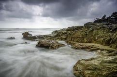 Wellen, die den Felsen an der Küste schlagen weiche Blickwelle und drastische dunkle Wolke Stockfotos