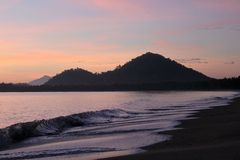 Wellen, die den gemalten Sonnenaufgang holen Stockfotos