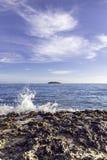 Wellen, die die Felsen in einer Insel einlaufen stockbild
