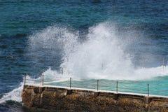 Wellen, die in Felsenpool spritzen Stockbilder