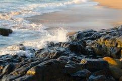 Wellen, die gegen beleuchtete Felsen spritzen Stockfotografie