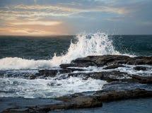 Wellen, die gegen die Felsen spritzen Lizenzfreies Stockfoto