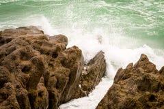 Wellen, die gegen die Felsen zusammenstoßen Stockfotografie
