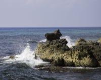 Wellen, die gegen Felsen abbrechen stockfotografie