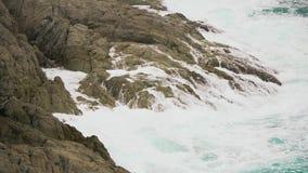 Wellen, die gegen Felsen im Ozean, Gischtspritzen zusammenstoßen stock video