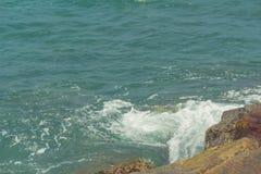 Wellen, die gegen Felsen spritzen stockfotografie