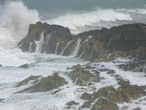 Wellen, die gegen Felsen zusammenstoßen Stockbilder