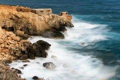 Wellen, die gegen hohe Klippen zusammenstoßen Stockbilder