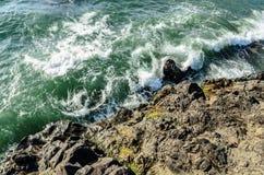 Wellen, die gegen Klippe, Ansicht von der Spitze brechen Schattenbild des kauernden Geschäftsmannes Lizenzfreie Stockfotos