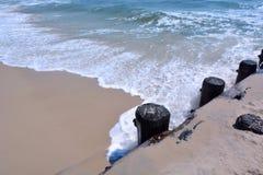Wellen, die sich waschen, um entlang Schutzwand unterzustützen Stockfotos